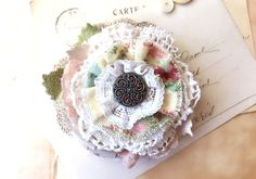 This rustic shabby chic fabric flower pin in pretty pastel colors is a favorite in our new Spring Collection. This brooch features layers of hand-cut and sewn textiles, vintage lace and burlap leaf details. The bloom is so full of pretty textures and mixed patterned fabrics. The unique metal mirror back button makes an eye-catching centerpiece on this one-of-a-kind accessory. • Pin measures 4 inches. • Locking clasp pin is sewn onto the back and covered with very soft wool/rayon felt. C...