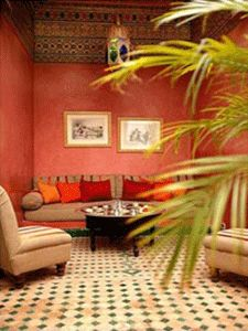 moroccan style courtyard with decorative pillows in red colors, pink walls and tiled floor