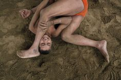 """Wrestlers fight at a permanent mud wrestling ring at """"Sia Ram bhajan samati akhaara"""", a traditional Indian wrestling training centre, on the banks of the river Ganges in Kolkata February 17, 2013. India's government will seek the support of other countries where wrestling is popular to help the sport remain an Olympic discipline, the country's sports minister said on Wednesday. REUTERS/Rupak De Chowdhuri"""