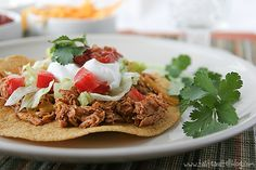 Slow Cooker Chicken Tostadas | This recipe is as simple as throwing some ingredients in a slow cooker.  Let them cook together, and then all you have left to do is top your tostadas.  Hands on time is probably 15 minutes – if you count the time it takes to cut up the veggies and grate the cheese. | From: tasteandtellblog.com