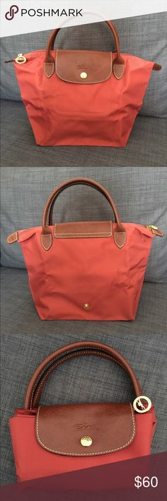 "Longchamp Mini Le Pliage in Terracotta Longchamp Mini Le Pliage in Terracotta.  New without tags. Water-resistant nylon tote that folds into a small rectangle when not in use -- perfect for travel!   Measures: 8 1/4""W x 8 1/4""H x 5 1/2""D             Handle: 3 1/2"" drop                                                 Top zip with snap-flap closure. Interior cell phone pocket. Water-resistant lining. Folds flat for storage. Nylon with leather trim. Longchamp Bags Mini Bags"