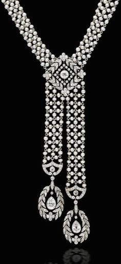 A belle époque pearl and diamond sautoir, J.E. Caldwell, circa 1910, the woven seed pearl necklace centering a lozenge-shaped panel of old European-cut diamonds in a foliate motif suspending an asymmetrical pendant each with terminals of pear-shaped diamonds within diamond foliate borders; signed J.E.C. & Co, no. F3699; mounted in platinum; length: 18in.