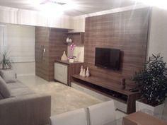 sala integrada com a varanda com a churrasqueira camuflada pelo painel  de madeira