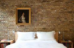 Schlafzimmer Ziegelwand als Hintergrund für das weiße Bett