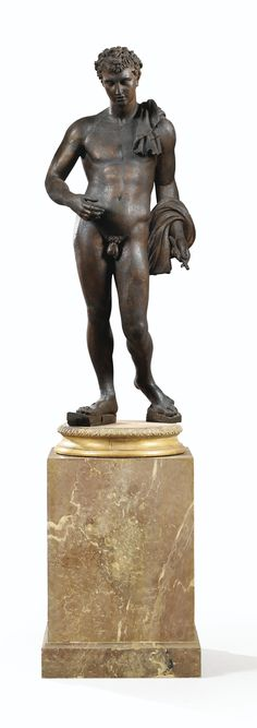 AN ITALIAN PATINATED WOOD FIGURE OF THE BELVEDERE ANTINOÜS, After the Antique; On a patinated wooden base imitating marble ; height 29 1/2 in., height (overall) 55 in.