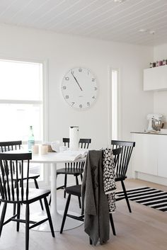 Black and white kitchen and dining area with huge clock