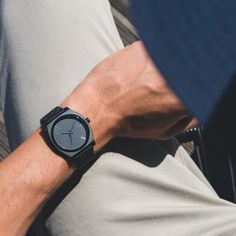Feeling the weather (almost) warming up with the Nixon Time Teller watch, a timepiece for all seasons and all reasons. This leather watch is for men's fashion, the case of the watch is black and in metal. Some details of the face are colorful and shiny