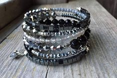 This 6 coil bracelet is made with stainless steel memory wire - will adjust to the size of your wrist and no chance of breaking. This will ensure you will have this bracelet for a long time. Materials include an assortment of sizes and shapes of silver, black and clear beads including