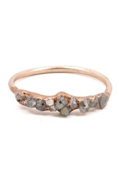The diamonds clustered atop this ring are displayed in its natural, raw glory. They're then hand-painted with copper and sealed for a dazzling finish. Stones are left in their most natural form to cre