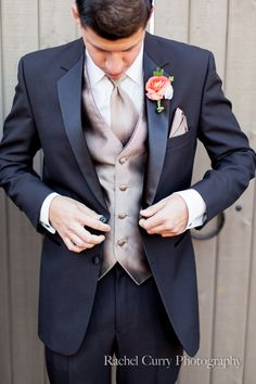 Groom in a navy tux with a gold tie and vest.Coral Boutonniere