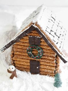 Use pretzel rods to craft up a rustic log cabin gingerbread house to serve as the centerpiece for a holiday dessert table or mantelscape. Get the step-by-step instructions. Gingerbread House Parties, Christmas Gingerbread House, Noel Christmas, Christmas Goodies, Christmas Treats, Christmas Baking, Winter Christmas, Christmas Decorations, Xmas