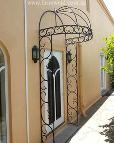 A wrought iron door canopy frames the doorway with a lovely arch, giving a plain wall an elegant look. North Adelaide, South Australia.