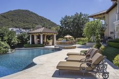 Sit by the pool on a sunny day in this stunning backyard! Outdoor kitchen and dining area under the cabana. Perfect for a family gathering.