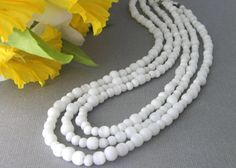 This beautiful white cats eye beaded necklace has three flowing strands at various lengths. The cats eye gemstones have reflective light gray