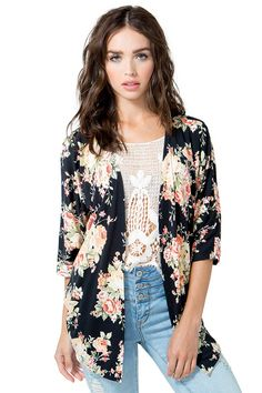A slinky and feminine open cardigan, featuring a sweet rose print throughout on a black grounding. Dolman half sleeves. Pointed ends. Unlined. $14.50