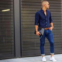 Acheter la tenue sur Lookastic: https://lookastic.fr/mode-homme/tenues/chemise-a-manches-longues-jean-skinny-baskets-basses/19299   — Chemise à manches longues bleue marine  — Montre en cuir brun clair  — Ceinture en cuir tressé brun  — Pochette en cuir noire  — Jean skinny bleu  — Baskets basses blanches