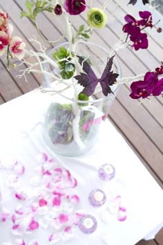 Table centerpiece with white branches, purple - pink and green flowers / orchids, and purple butterflies. Purple, Pink and Green. Photo Credit : A. Mordant  Contact us at http://www.wedotahiti.com/en/tahiti-wedding-planner-contact-form/ #tahitiweddingplanner #tahitiweddingpackage