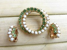 Up for sale is this brooch and clip on earring set. The brooch has two interlocking circles, one of green rhinestones and the other is white milk
