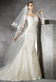 Pronovias. Tulle mermaid dress with long sleeves with beige underlay. Off-the-shoulder neckline with sheer illusion tulle overlay. Long sheer sleeves with appliqu�s.