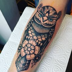 Black and white blue-eyed owl tattoo. Perched on a Yorkshire rose