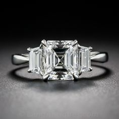 A bright and shining, icy-white, almost square (almost Asscher-cut) diamond, weighing 2.02 carats and accompanied by a GIA diamond grading certificate stating: F color - VS2 clarity, is elegantly presented in platinum between a pair of trapezoid diamonds (together weighing .56 carats) in this absolutely stunning and timeless engagement ring, newly crafted to showcase the vintage center stone.