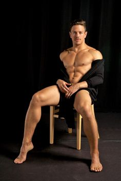 Muscular twink striking sexy poses in a studio