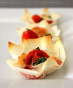 Margherita Pizza Cups- press spring roll wrappers into muffin pan. In each pastry cup, add a cherry tomato, a cube of mozzarella and a fresh basil leaf.  Bake for 10-15 minutes, until the pastry is crispy and the cheese is melted and slightly browned.
