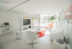 La zona de día de un moderno y luminoso ático en el centro de Valencia se compone se articula a partir de un mueble televisor realizado en carpintería en exclusiva para el proyecto, que hace de divisor entre la zona de salón y comedor. El suelo de microcemento y la ausencia de tabiquería aportan una gran sensación de amplitud. En la imagen: sofá Duny de Tonin Casa tapizado en Ecopiel blanca, mesa auxiliar Kos de Tonin Casa, sillón Peel de Varier y alfombra Zoom Rojo de Nanimarquina.