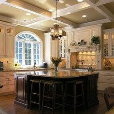 Coffered ceiling, light cabinets, some glass/some solid cabinet fronts, multi drawers, beautiful square island for a square kitchen, contrasted island vs cabinet color, pot filler, and more