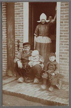 Gezin in de deur. 1900-1910. Volendammer gezin poseert in de deuropening. De…
