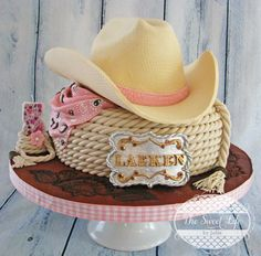 Cowboy Hat and Buckle Cake - YEEHAW! This cake has been such a ball to make AND to hear all the lovely comments about it! The crown of the hat and the lasso tier are both cake and the brim of the hat and buckle are gumpaste. I extruded 3 pipes of fondant and then, twisted together to form the lasso. The beautiful board was accomplished using Ciccio Cakes, fantastic tooled leather tutorial. Thank you so much for the opportunity to share and hope you all like it!