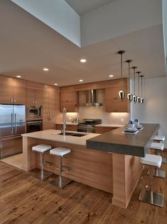 Inspiration for a mid-sized contemporary u-shaped open concept kitchen with a double-bowl sink, flat-panel cabinets, medium tone wood cabinets, beige backsplash, stainless steel appliances and medium tone hardwood floors. — Houzz Clean lines, wood focus, countertop heigh variation — johnpwray