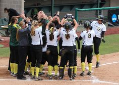Color photo of University of Oregon softball player Christie Nieto (#17) being greeted at home plate by teammates after hitting a grand slam during an NCAA Regional game against Brigham Young on May 18, 2012 at Howe Field and won by the Ducks 6-4.
