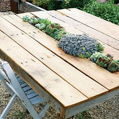 Succulents fill a long container (with drain holes) set into the top of this table built from recycled wood. By Far Out Flora.