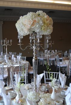Beautiful Creamy white hydrangea and roses make for a beautiful arrangement on the top of a candelabra