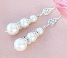 These white pearl bridal earrings are feminine with a little bit of bling. These feature graduated white glass pearls tiered with crystal studded rondelles. These pearls are beautiful quality, they ha