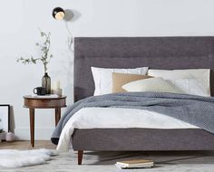 Scandinavian Designs - Curate a modern bedroom with the Tambur bed. The tall headboard and tapered legs inspire visions of the best design age. Featuring a platform-style frame, there is no need for boxsprings. Chic charcoal grey upholstery envelops the frame and complements the solid wood legs.