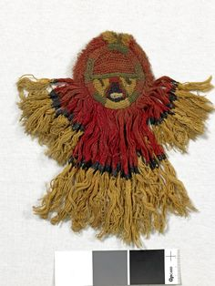 Tassel; textile; camelid; simple looping element; cross-knit looping around face and on nose; stem stitch on cheek; fringe forming 'body' of figure is sewn to hold together; almost all cut except a few still looped; red, tan, dark brown, green, white. Chancay, 900-1430.  Registration number: Am1919,1119.17