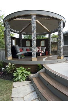 """The circular lounge includes privacy barriers with glass panel inserts, a round pergola with custom shade sails, faux stone post covers, and a curved sectional couch wrapping around a gas fire feature.  From """"Decked Out"""" project """"The West Coast Deck"""".  Deck Design by Paul Lafrance Design."""