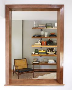 An internal window offers a glimpse of plywood shelves and a mid-century Danish Modern armchair.