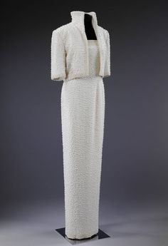Designed by Catherine Walker, this white silk crepe sheath dress and matching high collared jacket embroidered all over with simulated pearls and white sequins was dubbed the 'Elvis' dress by Diana. The dress raised $ 151,000 for charity at the Christie's auction.