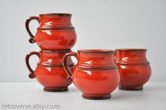 Set of 4 West German pottery coffee mugs.  Round shape in red-hot glossy glaze over a white clay base.  Large in size size for vintage mugs--they hold about 10 oz.