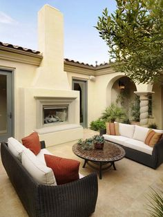 The standout element in this courtyard is the stucco fireplace. Sleek sofas add modern style and comfort to the outdoor escape.
