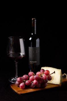 botellas-alameda_colectivo-verbena_070 - Fotografía de producto. Bodegón sobre fondo negro de una botella de vino con una copa, uvas y una cuña de queso para el Catering Alameda
