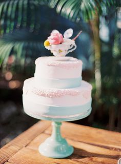 sweet wedding cake with a teacup on top