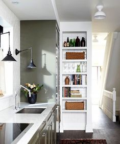 Olive walls in the kitchen with white bookshelf and industrial wall sconces