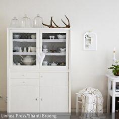 Ein weißer Küchenschrank im Vintage-Stil birgt viel Platz für Küchenutensilien. Mit Glashauben und einem dekorativen Ast wird er schön inszeniert und sorgt…