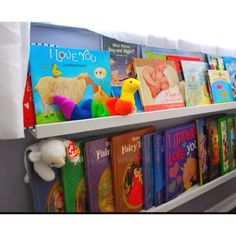 Shelving by ikea, made into under the window front facing bookshelves, good idea for baby books because of all the different sizes.