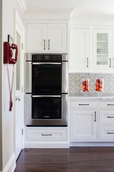 Stunning kitchen features white cabinetry painted Benjamin Moore White Dove accented with oil-rubbed bronze hardware alongside carrera marble counters and a hand painted white and gray mosaic tiled backsplash which highlights stainless steel double ovens beside walls painted Benjamin Moore Revere Pewter adorned with a red vintage phone from Target...... I love that backsplash!! (love this site, it gives a lot more info for a room photo)