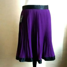 Purple pleated skirt. Nwt size small fits like a sz M. Has a black bow at the back. Skirts